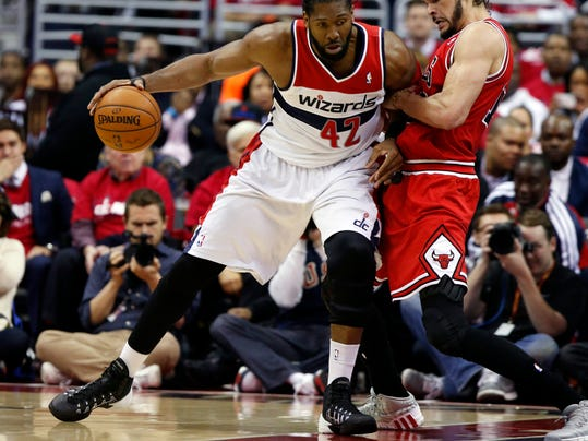 Washington Wizards forward Nene (42), from Brazil, drives against Chicago Bulls center Joakim Noah (13) in the first half of Game 3 of an opening-round NBA basketball playoff series on Friday, April 25, 2014, in Washington. (AP Photo/Alex Brandon)