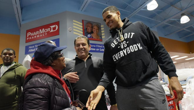 Edna Murray-Scott, left, gets a turkey from Basim Shina, center, and Pistons forward Tobias Harris at Imperial Fresh Market in Detroit.