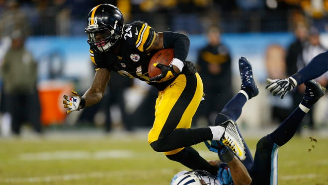 Former Spartan Le'Veon Bell  of the Pittsburgh Steelers is defended by  George Wilson #21 of the Tennessee Titans in the fourth quarter at LP Field on November 17, 2014 in Nashville, Tennessee. The Pittsburgh Steelers won, 27-24.