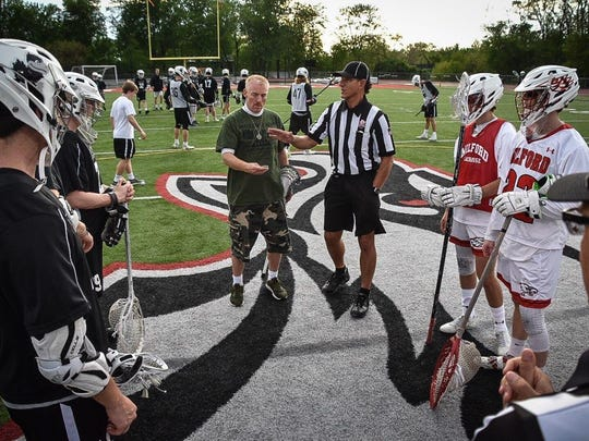 Sam Landis takes part in the coin toss at Milford lacrosse's