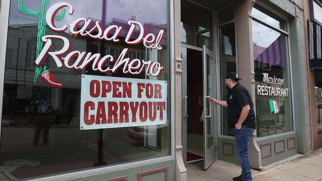 Danny Sanchez, co-owner of Casa Del Ranchero Mexican Restaurant, walks into his restaurant on West Tuscarawas Avenue on May 12, 2020, in Barberton, Ohio. As more businesses open following coronavirus shutdowns, the number of jobless claims in Ohio and elsewhere has begun decreasing.