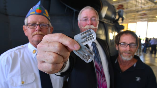 Rick Kibbey (center) holds his father's dog tags with his brothers Dave (left) and John. A ceremony was held at Patrick Air Force Base Monday morning to return the dog tags to the sons of Air Force Col. Richard A. Kibbey, who was killed in Vietnam in 1967 while flying a rescue mission. His dog tags were recently discovered by a local farmer in Vietnam.