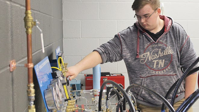 Fairview High senior Geoff Trigleth checks a pressure gauge on the pneumatic trainer during the Feb. 28 open house.