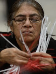 Francisca Soreano weaves a basket together at the Hispanic Coqueta booth Saturday at the New Leaf Farmer's Market in the KI Convention Center.