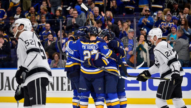 St. Louis Blues defenseman Carl Gunnarsson (4) is congratulated by teammates after scoring against the Los Angeles Kings during the second period at Scottrade Center.