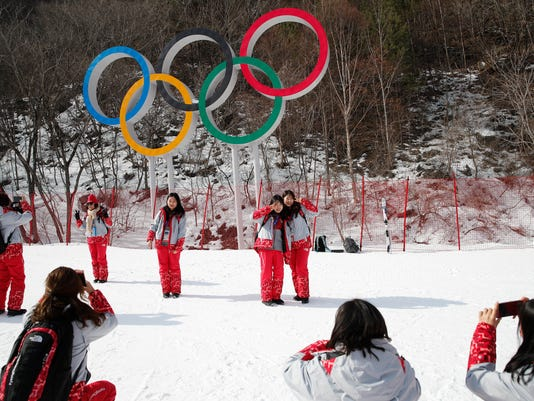 Volunteers take photos in front of the Olympic rings near the finish area during men's downhill training at the 2018 Winter Olympics in Jeongseon, South Korea, Friday, Feb. 9, 2018. (AP Photo/Christophe Ena)