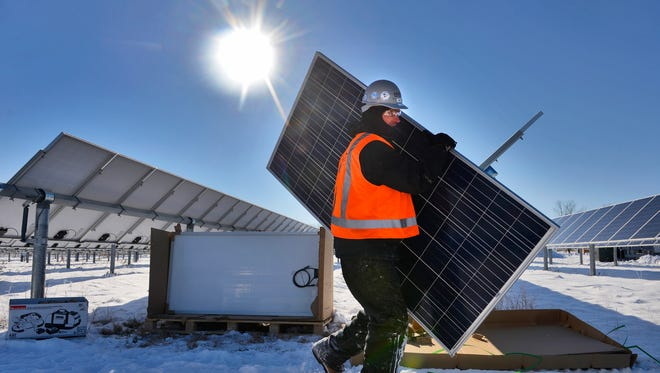 Electrician Tim Bode of Hunt Electric, St. Paul, carries a solar panel as he and others work to install an array of 616 new panels Friday, Nov. 14 in the St. John's Abbey Solar Farm. The new panels are more efficient than the existing ones but they will not follow the sun through the sky as the others at the farm do.