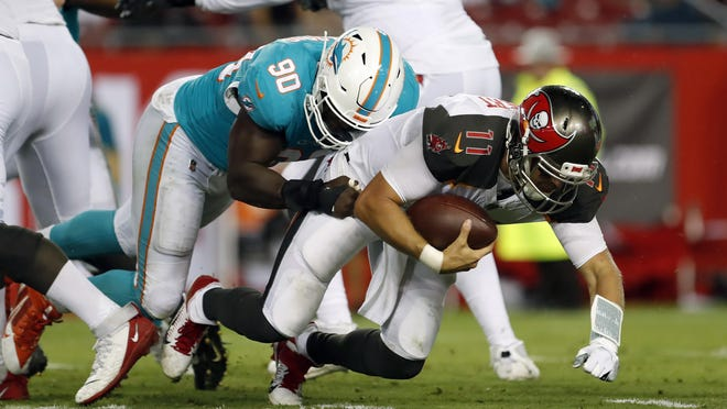 Miami Dolphins defensive end Charles Harris sacks Tampa Bay Buccaneers quarterback Blaine Gabbert during the first half of an NFL preseason football game.
