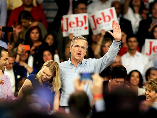Former Florida Gov. Jeb Bush, center, waves to the crowd while joined onstage by son George, from left, daughter-in-law Amanda, and wife Columba, far right, as he formally joins the race for president with a speech at Miami Dade College, Monday, June 15, 2015, in Miami. (AP Photo/David Goldman)