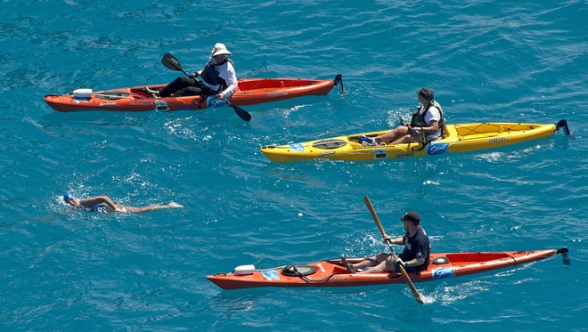In this photo provided by the Florida Keys News Bureau, 64-year-old Diana Nyad, positioned about two miles off Key West, Fla., is escorted by kayakers as she swims toward completion of her 110-mile trek from Cuba to the Florida Keys.