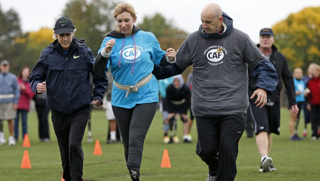 Heather Abbott, a spectator who lost her leg in the Boston Marathon bombings, runs along with Dan Connors, a physical therapist, and Joan Benoit Samuelson, a marathon runner, while wearing her new prosthetic that will allow her to run. Abbott attended an event coordinated by the Challenged Athletes Foundation on Sunday in Boston.