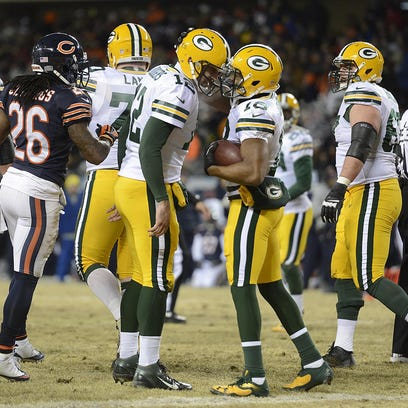 Packers receiver Randall Cobb (18) is congratulated by quarterback Aaron Rodgers after the two connected on a touchdown against the Bears in the 2013 regular-season finale.