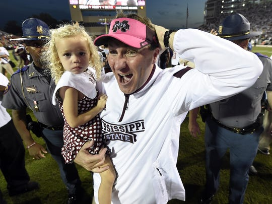 Mississippi State coach Dan Mullen carries his daughter, Breelyn, after MSU beat Auburn.