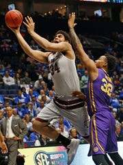 Texas A&M's Tyler Davis (34) shoots past LSU's Craig Victor II (32) during the first half of an NCAA college basketball game in the Southeastern Conference tournament in Nashville, Tenn., Saturday, March 12, 2016.