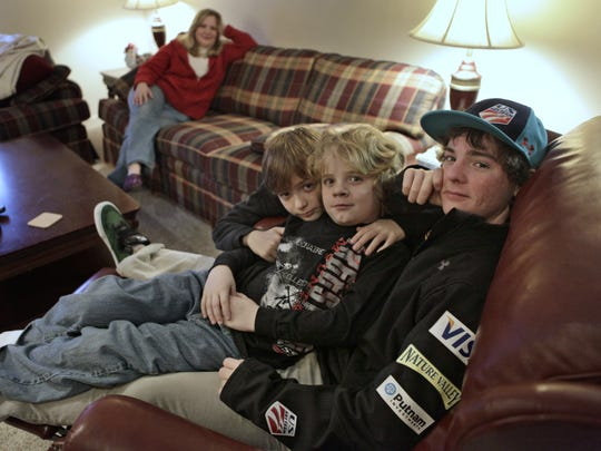 In this file photo from 2010, Pittsford freestyle skier Michael Lillis, aged 10, center, is pictured with Jonathon Lillis,  age 16, far right, and his younger brother  Chris, age 12, left, with his mother Jamie relaxing on the couch at far left.  Jonathon had just come home from a trip with the US Freestyle Ski team of which he is the youngest member. (Democrat and Chronicle, Photo by Annette Lein)