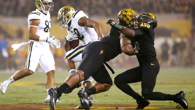 UCLA's Eldridge Massington runs for a touchdown after Arizona State's Damarious Randall (right) collides with a teammate in the first half on Thursday, Sept. 25, 2014 at Sun Devil Stadium in Tempe.