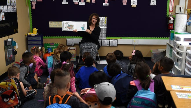 A teacher reads a story to her students at Booth Elementary School.
