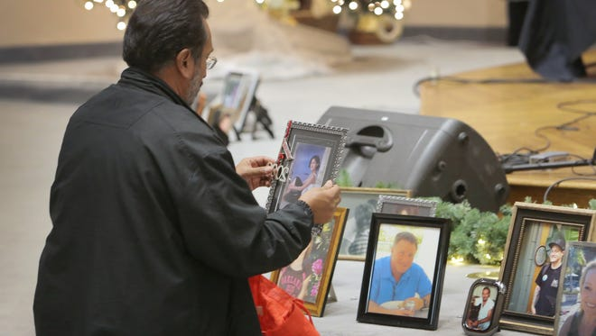 Joe Delira, of Ventura, places a photo of his daughter Amanda, who died in 2009, in a display at a Compassionate Friends candle lighting ceremony two years ago.