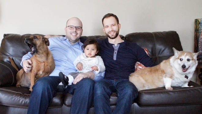 Brett Parlock, left, Leah Rose, 16 months, and Kevin Schaefer pose for a photo with their dogs Penny, left, and Riley at their Frankfort, Ill., home.