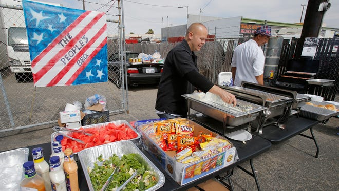 """Volunteer Jarrod Chambers, left, prepares one of the hot food trays as Oxnard chef and organizer Victor Ortiz gets ready to resume his cooking duty during the first """"People's BBQ"""" that was held on Monday in Oxnard. He and his volunteers fed between 150 to 200 homeless people in Oxnard."""