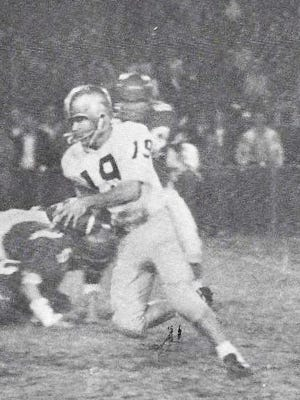 Quarterback Marcus Waters, 19, scrambles for yardage in the 1965 defeat of Dublin's Fighting Irish, 12-0, in Jaycee Stadium.