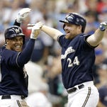 Milwaukee Brewers' Adam Lind, right, and Carlos Gomez, left, celebrate Lind's two-run home run against the Minnesota Twins during the eighth inning Sunday in Milwaukee.