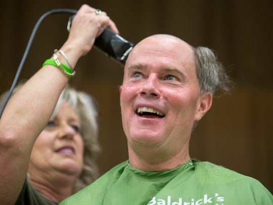 Mayor Joe Hogsett smiles as he has his hair clipped