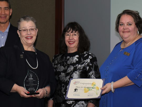 Mike Jung of the Commercial Appeal looked on while Beth Bates (center) and Stacy Miller (right) present the 2018 Sue Shelton White award to Jackson attorney, Mary Jo Middlebrook (right) on April 10 during the 9th annual Sterling Awards ceremony in the J. Walters Barnes Center at Jackson-Madison County General Hospital.