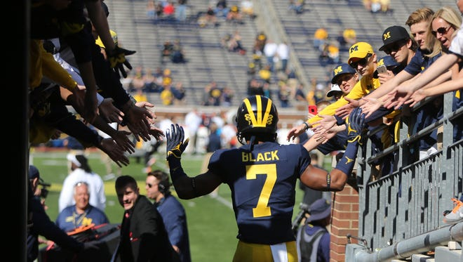 Michigan's Tarik Black high-fives fans on his way to warm up for the game against Cincinnati, Saturday, Sept. 9, 2017 at Michigan Stadium.