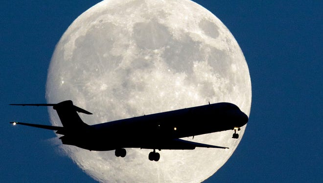 An airplane passes a nearly full moon as it  approaches Philadelphia International Airport on Sept. 7, 2014.