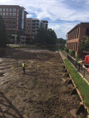A Greenville city worker surveys the dried up Reedy River.