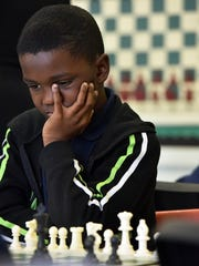 Nick Smith, 11, plays chess during class at the Franklin