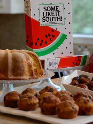 """The Junior League of Pensacola Florida's cookbook """"Some Like it South!"""" shown with sour cream poundcake, blueberry orange muffins and glazed sausage bites."""