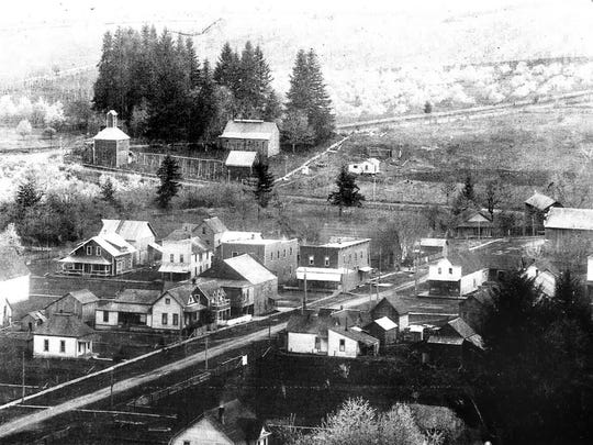 Scotts Mills is seen looking east about 1915. In addition to businesses and homes, a prune dryer can be seen across Butte Creek in Clackamas County.