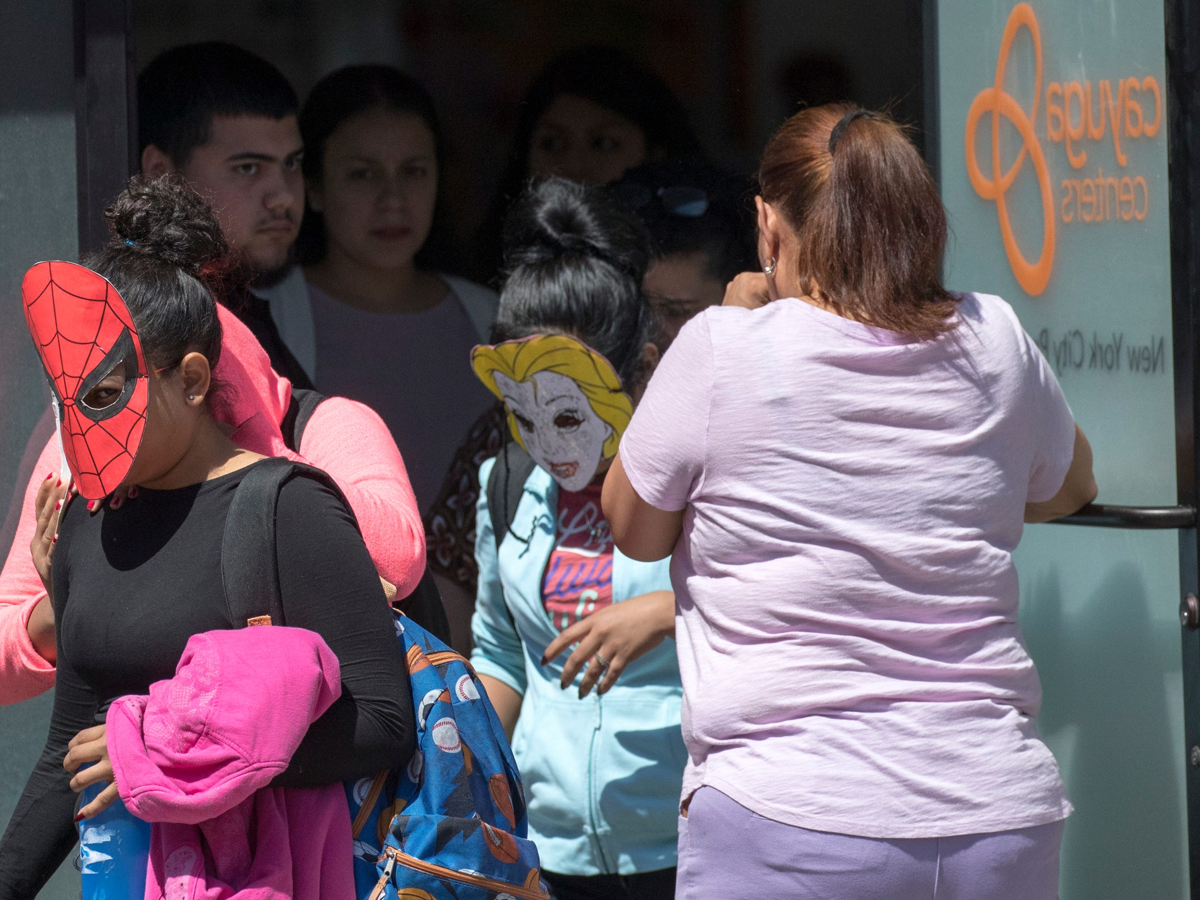 Children in homemade masks are escorted out of the Cayuga Centers facility on June 21, 2018, in New York. Mayor Bill de Blasio says he recently learned that migrant children separated from their parents by federal officials are being cared for in the facility.