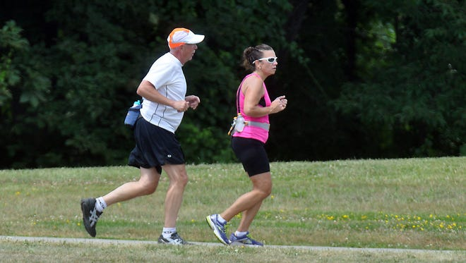 Dave Joseph from Novi and Pam Webert from Livonia go for a run at Kensington Metro Park.