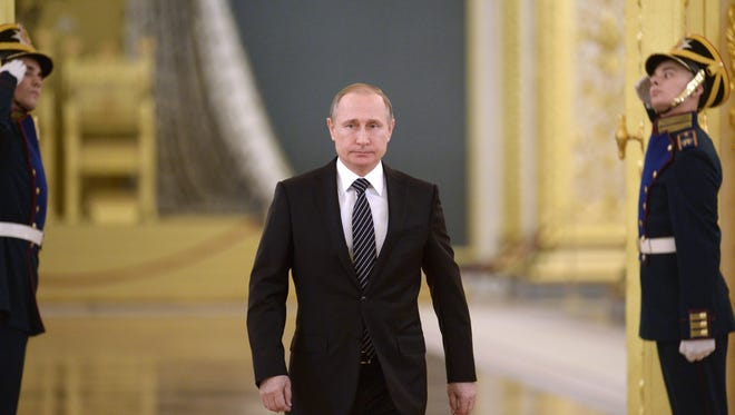 """Russian President Vladimir Putin walks in Moscow's Kremlin, Russia on Thursday, March 17, 2016. President Vladimir Putin says Russia can again build up its forces in Syria """"in a few hours"""" if necessary, and will continue striking extremist groups. Putin made the statement in the Kremlin Thursday while honoring Russian military officers who have taken part in the Syrian campaign."""