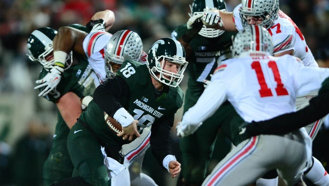 Nov 8, 2014; East Lansing, MI, USA; Michigan State Spartans quarterback Connor Cook (18) runs the ball during the second quarter against the Ohio State Buckeyes at Spartan Stadium.