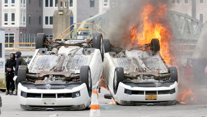 Protestors overturned and set fire to several cars in a parking lot across from Rochester's City Public Safety Building.