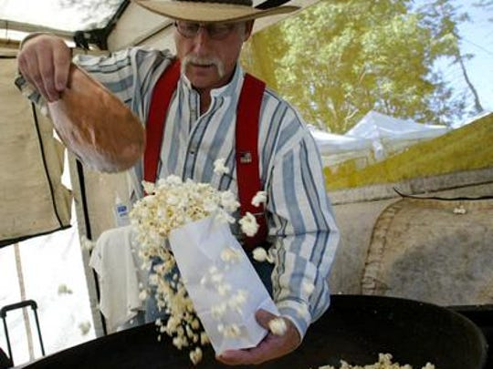 "Doug Gutenkunst bags freshly-cooked kettle corn at his vendor tent, ""Cowboy Kettle Korn"" at the Maple Fall Fest."