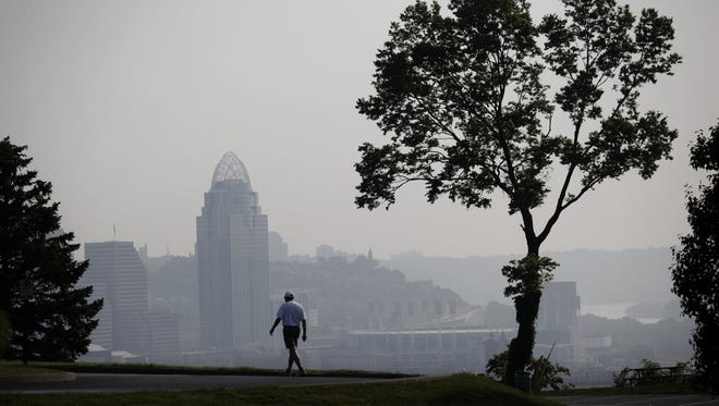 Charles Bucklew, Ludlow, Ky. walks in Devou Park in Covington, Ky. where the downtown Cincinnati, Ohio skyline is shrouded in haze.