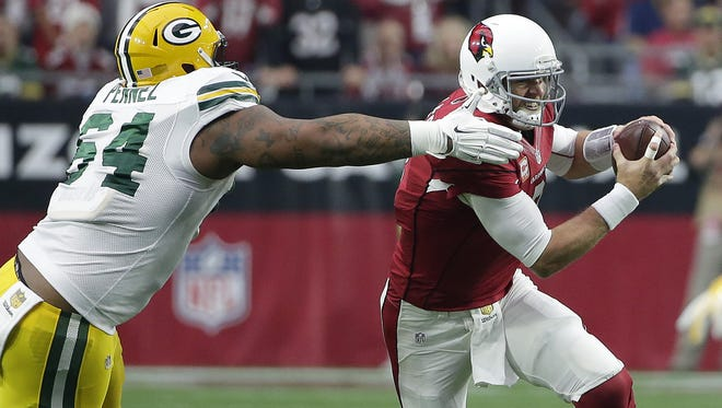 Green Bay Packers defensive end Mike Pennel (64) tries to grab Arizona Cardinals quarterback Carson Palmer (3) at University of Phoenix Stadium December 27, 2015.