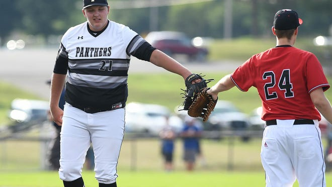 Perry graduate Brandon Scheetz touches gloves with McKinley's Carter Hoskins during the Federal League Senior All Star Doubleheader. Scheetz played all nine positions in the seventh inning of game two and also coached first base and third base during the double header.