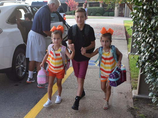 Morgen Johnson (center) walks his twin sisters Sammie and Maggie Johnson into Alexandria Country Day School for their first day of school on Wednesday.