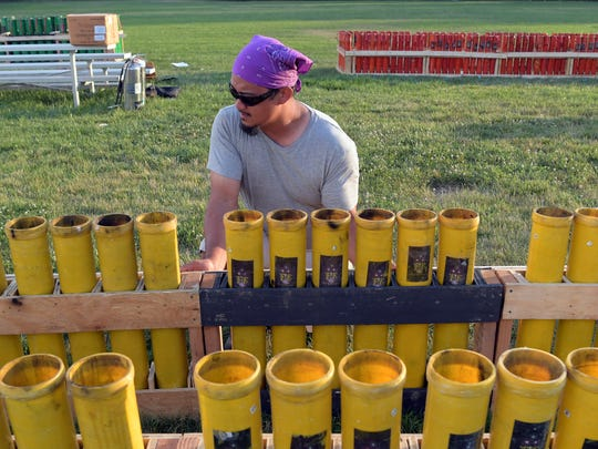 Fireworks Extravaganza employee Jacob Thomas secures a launch for 4-inch shells before the fireworks display he was working at a field at Red Lion Junior High School Tuesday, July 3, 2018. The company is based in Chesapeake City, Maryland. Bill Kalina photo