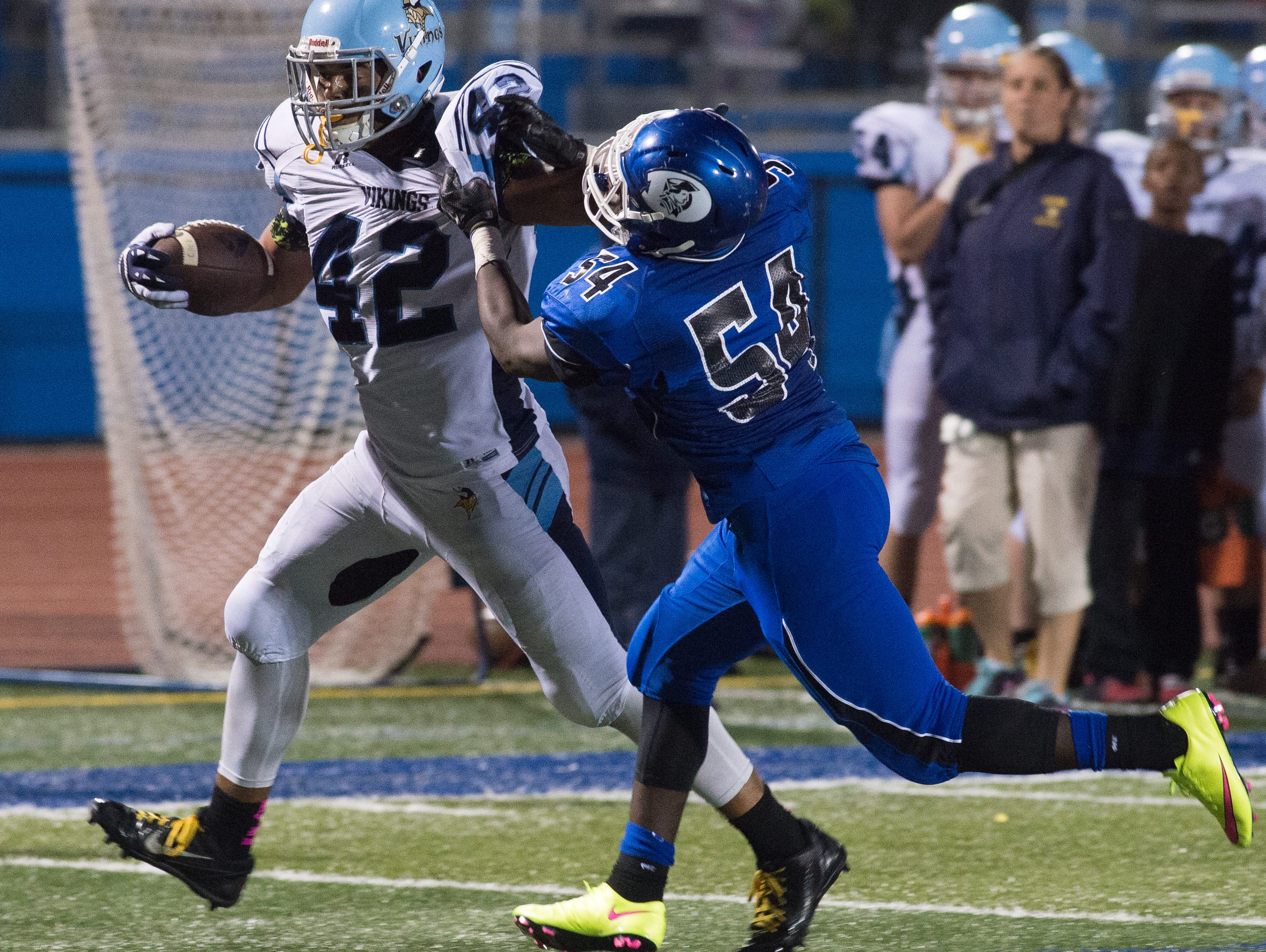 Cape Henlopen's Kolbi Wright (42) breaks a tackle attempt by Dover's Lawrence Horsey (54) in their 29-14 win over Dover.