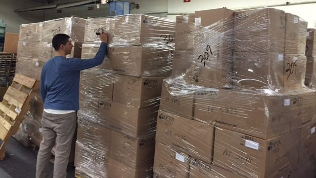 A staffer from the Afya Foundation in Yonkers prepares pallets of supplies for the refugee crisis in Greece and the Middle East.