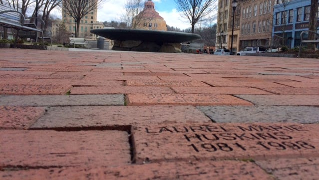 Fundraising bricks like this one near the bronze fountain at Pack Square Park have been put back in place.