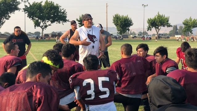 Orosi High head football coach Ben White speaks to his players after practice on Tuesday in Orosi.