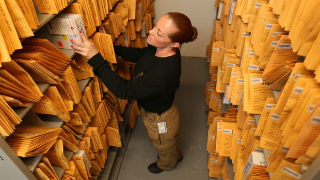 Officer Kelly Richards, an evidence and property technician for New Castle County Police Department, stands amongst the several envelops of crime related material along with a rape kits.